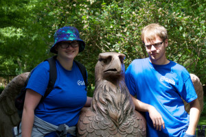 Haize and Dale posing with a sculpture of an eagle at the zoo.